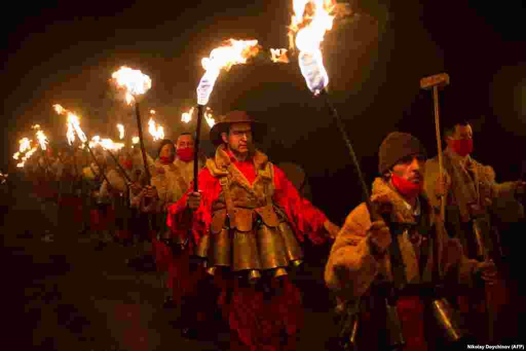 Болгарские танцоры в костюмах исполняют ритуальный танец с горящими факелами во время карнавала Кукери в селе Долна Секирна, 13 января. (AFP/Николай Дойчинов)