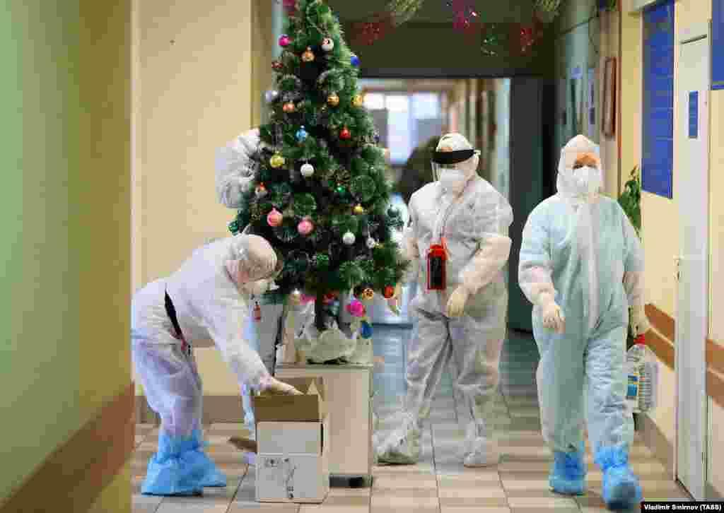 Медици в предпазно облекло украсяват елха в болницата в Иваново, в която лекуват и пациенти с COVID-19.