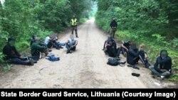 Снимка от 3 юли, на която се виждат мигранти, задържани от литовската полиция на границата с Беларус.