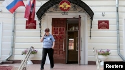 Полицейский у входа в миграционную службу России. Москва, 16 июля 2013 года.