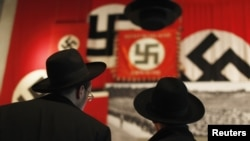 Ultra-Orthodox Jewish visitors look at a display of Nazi flags at Yad Vashem's Holocaust History Museum in Jerusalem.