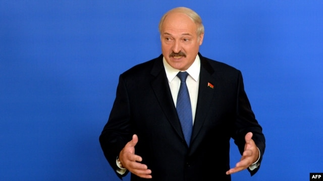Belarusian President Alyaksandr Lukashenka speaks with journalists at a polling station in Minsk on October 11.