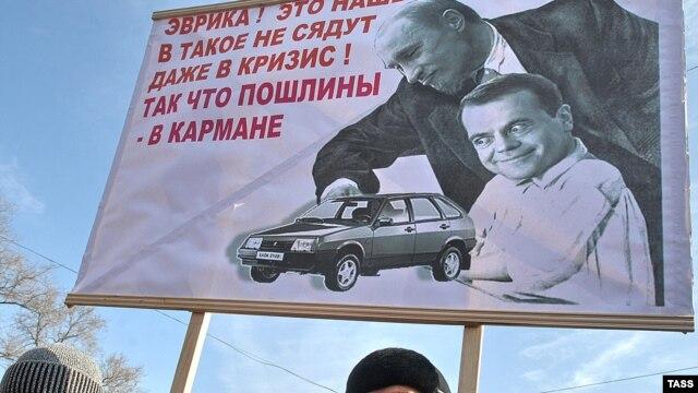 Шеруге шыққандар көлік салығына енгізілген кедендік өзгеріске байланысты Путин мен Медведевті келемеждеп салған суретті ұстап келеді. Ресей, Владивосток.