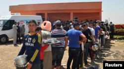 Turkey -- Displaced people from the minority Yezidi sect, fleeing violence in Iraq, line up to receive food as they take refuge in the southeastern Turkish town of Silopi, near the Turkish-Iraqi border crossing of Habur, August 13, 2014