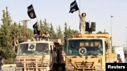 Militant Islamist fighters wave flags as they take part in a military parade in Syria's northern Raqqa province on June 30 to celebrate the announcement of a new Islamic Caliphate by ISIL.