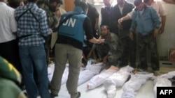 Чальцы сьледчай камісіі ААН аглядаюць целы загінулых падчас масакры ў Хоўле. 26 траўня, 2012