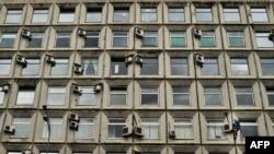 Рабочий проводит обслуживание кондиционеров, установленных на фасаде здания в Москве. 19 августа 2015 года.