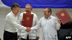 Президент Колумбії Хуан Мануель Сантос (л) підписує мирну угоду з лідером ФАРК Тимолеоном Хіменесом (п) у присутності президента Куби Рауля Кастро, Гавана, 23 червня 2016 року