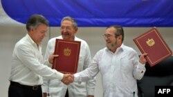 Президент Колумбии Хуан Мануэль Сантос (слева) и глава ФАРК Тимолеон Хименес подписали мирное соглашение в Гаване 23 июня 2016