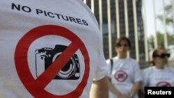Участникам пикета раздали майки со знаком, запрещающим фотографировать. Этот знак стал своего рода символом протестных акций в поддержку фотокорреспондентов. Собравшиеся – около двадцати журналистов