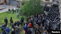 Ukrainian Interior Ministry troops stand in formation as pro-Russian supporters gather in the courtyard of the regional administration building during an attack by activists on the building in Luhansk on April 29.
