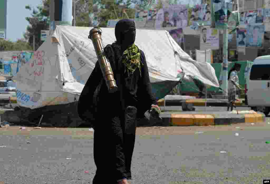 A woman from the southern Yemeni separatist movement, who oppose the Shi'ite Huthi rebels, walks carrying a rocket container, which she seized from the Badr military camp, in the southern city of Aden. (AFP/Saleh al-Obeidi)