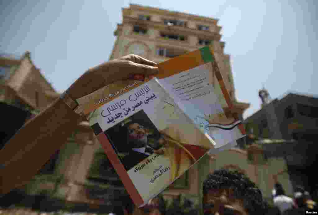 "A protester holds a book titled ""President Morsi Building a New Egypt"" in front of the headquarters of the Muslim Brotherhood in Cairo's Moqattam district."