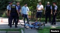 Полицейские стоят над задержанным мужчиной на месте нападений в центре Алматы. 18 июля 2016 года.