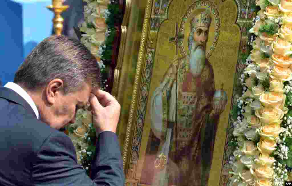 Ukrainian President Viktor Yanukovych crosses himself in front of an icon during a service and ceremony in Kyiv on July 27.