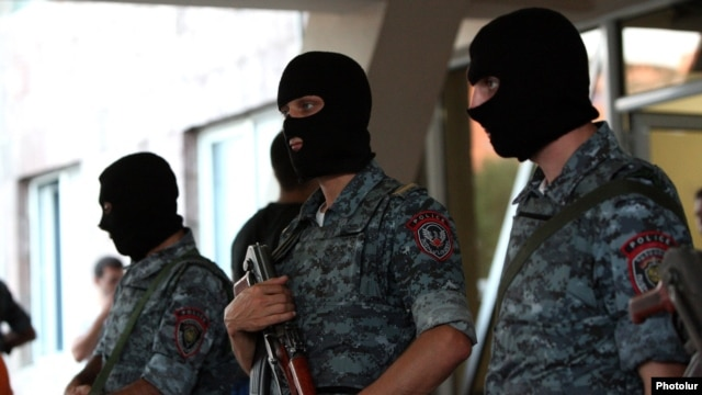 Armed police officers guard the entrance to a hospital in Yerevan where opposition gunmen wounded by security forces are receiving medical aid on July 29.