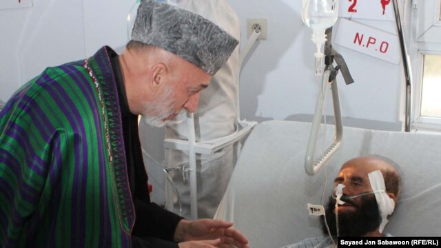 Afghan President Hamid Karzai visits victims of the blast in Kabul on December 7.