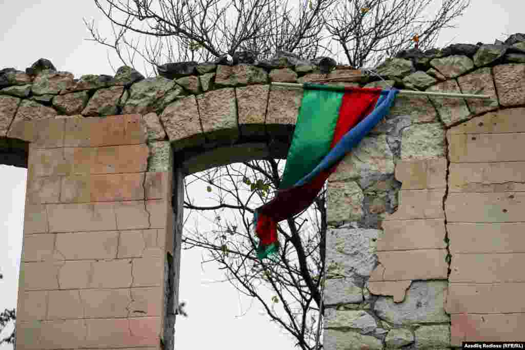 An Azerbaijan flag is draped over the ruins of a destroyed military recruitment office in the recaptured city of Fuzuli on November 18.