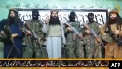 A video released by a faction within the Pakistani Taliban on January 22 shows their leader, Umar Mansoor (center), with militants delivering a statement from an undisclosed location.