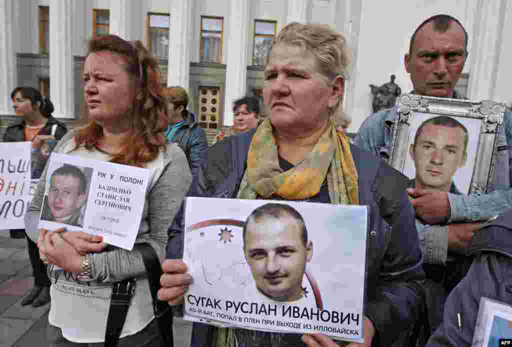 People hold pictures of relatives captured by pro-Russian separatists in eastern Ukraine during a rally in front of the Ukrainian parliament in Kyiv. Protesters demanded assistance in securing the release of the 29 prisoners, mainly servicemen from the Ukrainian forces. (AFP/Yuriy Kirnichny)