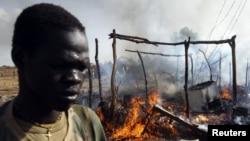 Суданский военный проходит рядом с дымящимся строением.