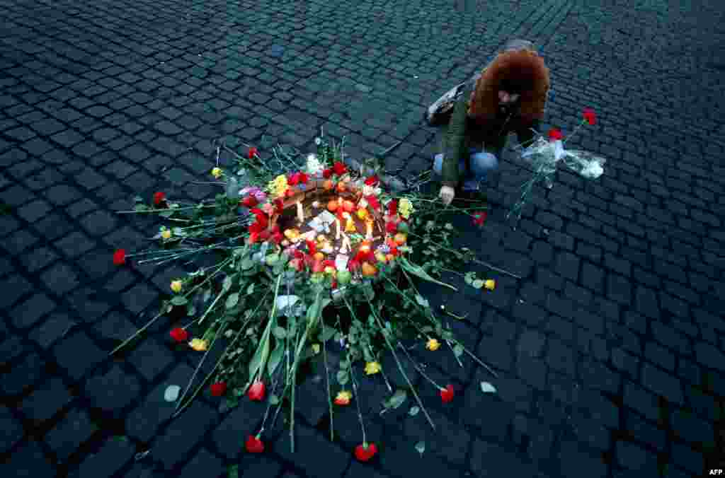 A woman places a flower on February 21 near the site in central Kyiv where an antigovernment protester was killed during clashes with police the previous evening. (AFP/Sergey Gapon)