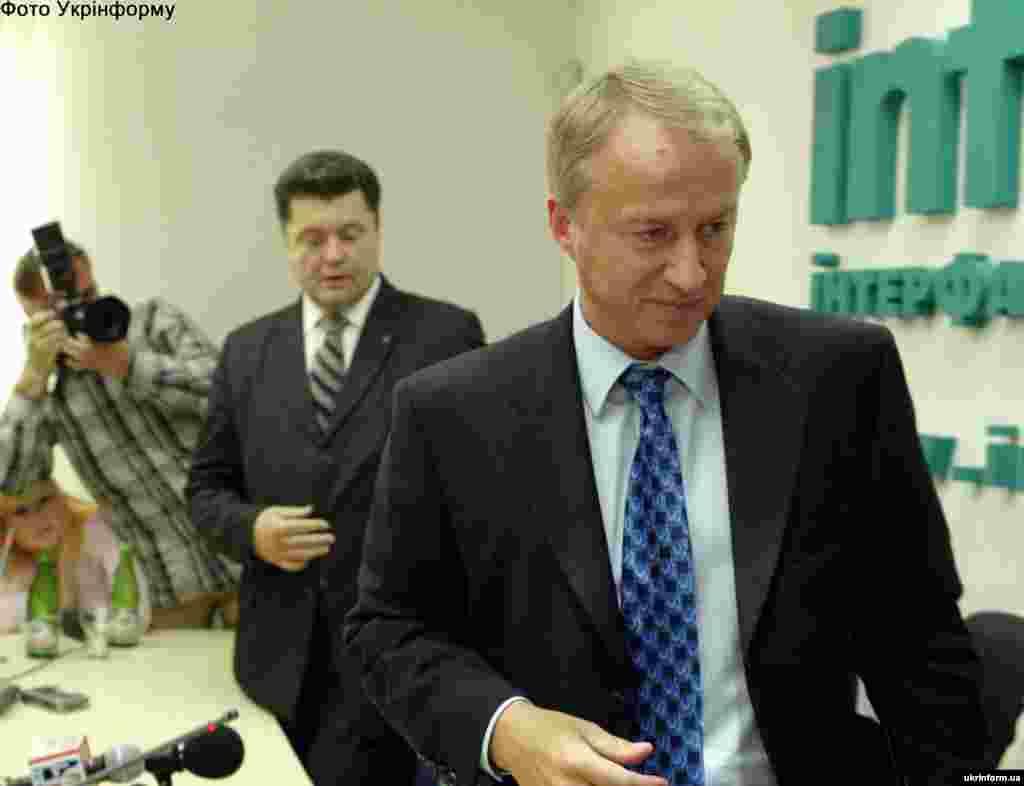 У 2005 році тодішній держсекретар Олександр Зінченко звинуватив Петра Порошенка, який обіймав на той час посаду секретаря РНБО, в корупції та вимагав від нього відокремлення бізнесу від влади. Зінченко переконував, що Порошенко контролює правоохоронні органи та судову гілку влади з метою відстоювання своїх бізнес-інтересів. Через три дні після цих звинувачень Порошенко оголосив про свою відставку. Тоді проти нього відкрили кримінальну справу, але згодом суд не встановив фактів злочину і зобов'язав Зінченка спростувати свою заяву. На фото: З журналістами після прес-конференції колишнього державного секретаря України Олександра Зінченка спілкувався секретар РНБОУ Петро Порошенко. Київ, 5 вересня 2005 року