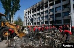Завалы около сгоревшего здания Горсовета Мариуполя разбирают работники местных предприятий, принадлежащих Ринату Ахметову