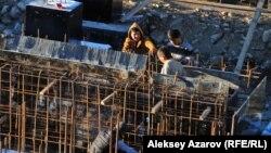 «Көкжайлау» тау шаңғысы курортына арналған қосалқы электр станциясы құрылысы орнында жүрген жұмысшылар. Алматы, 25 қазан 2015 жыл.
