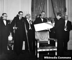 Контр-адмирал Кэри Грейсон, главный хирург Военно-морских сил США и личный врач президента Вудро Вильсона, вручает президенту Франклину Рузвельту чек на миллион долларов – эти средства, вырученные от продажи билетов на бал по случаю дня рождения президента, стали вкладом в Фонд Вормс-Спрингс, специализирующийся на помощи больным полиомиелитом. Май 1934 года. Из коллекции Библиотеки Конгресса США. © Harris & Ewing