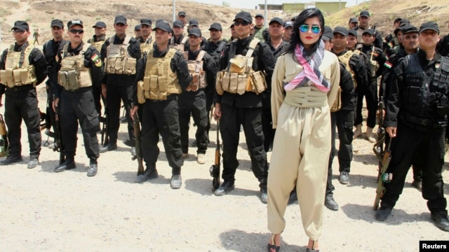Kurdish pop star Helly Luv poses in front of Kurdish Peshmerga troops at a base in Dohuk.