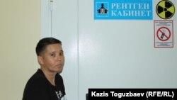 Айнур Худабаева возле металлической двери в рентген-кабинет, куда занесли ее сестру больную заключенную Гаухар Худабаеву. Поселок Отеген-батыра Алматинской области, 20 июня 2019 года.