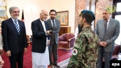 Afghan President Ashraf Ghani (2 - L) presents Afghan Army soldier, Esa Khan (C) with the keys to a new flat in recognition of his bravery in an attack by armed fighters on the Afghan Parliament in June 23.