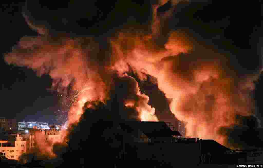 Вибухи освітлюють нічне небо над будівлями в місті Газі, коли ізраїльські сили обстрілюють палестинський анклав, ранок 18 травня 2021 року