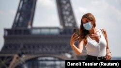 Një grua mban maskën mbrojtëse në Paris.