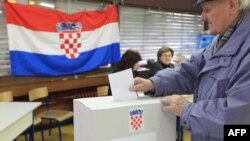 Croatia -- A man casts his ballot at a polling station in Zagreb, 22Jan2012