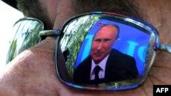 Көрермен көзілдірігіне шағылысқан Ресей президенті Владимир Путиннің телевизордағы бейнесі. Севастополь, 17 сәуір 2014 жыл.
