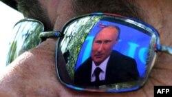 Видеокадр с президентом России Владимиром Путиным отражается на линзе очков телезрителя. Севастополь, 17 апреля 2014 года.
