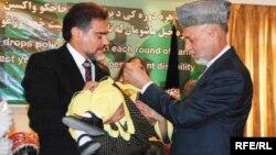 Ауғанстан президенті Хамид Карзай (оң жақта) полиомиелит вакцинасын балаға тамызып тұр. Ауғанстан, Кабул, 26 шілде 2009 жыл.
