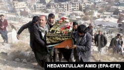People attend the funeral of one of the victims of a suicide bomb attack in Kabul on January 28.