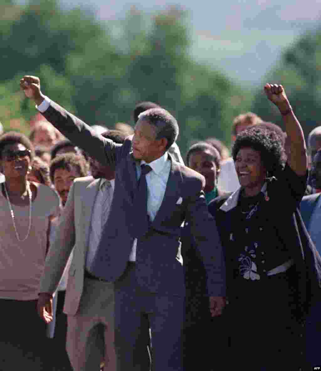 Nelson and Winnie Mandela raise their fists and salute a cheering crowd upon Nelson's release from prison after 27 years.