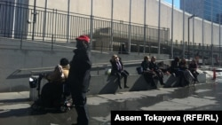 Женщины сидят у здания ООН, где проходит 59-я сессия Комиссии ООН по статусу женщин. Нью-Йорк, 9 марта 2015 года.
