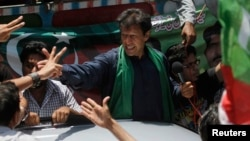 Imran Khan, chairman of the Pakistan Movement for Justice party (PTI) party, greets supporters after his visit to the mausoleum of Mohammad Ali Jinnah during an election campaign in Karachi earlier on May 7.