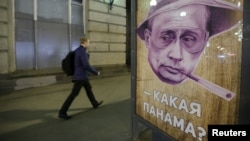 """A man walks past a poster depicting Russian President Vladimir Putin and reading """"Which Panama?"""" at a bus stop in Moscow on April 6."""