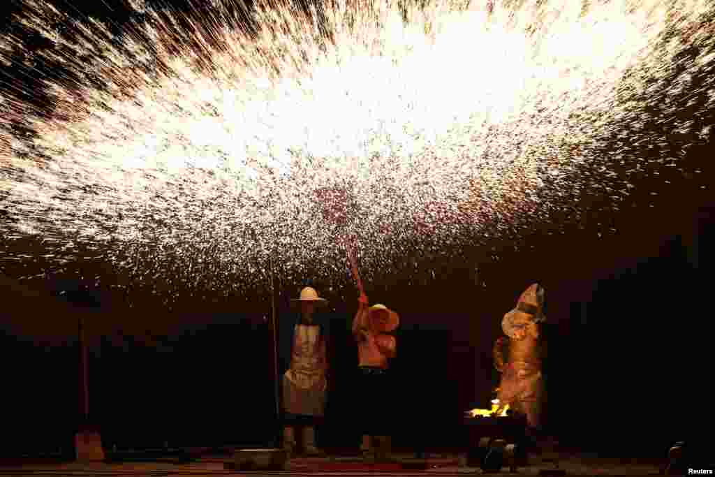 Folk artists create sparks with molten iron during a performance in Hunan Province, China. (Reuters)