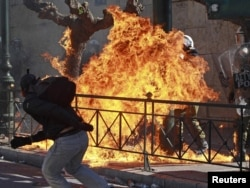 A youth throws a Molotov cocktail at police during riots in Athens last month. Will Rome be next?