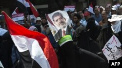 Supporters of the Muslim Brotherhood and ousted Egyptian President Muhammad Morsi hold his picture as they march toward Cairo University to demand his reinstatement on July 19.