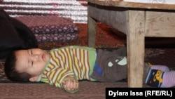 Внук Жанботы Боранбаевой лежит на коврике на полу. Шымкент, 13 марта 2017 года.