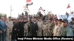 Հայդեր ալ-Աբադին, Իրաքի դրոշը պարզած, հայտարարում է ԻՊ-ի նկատմամբ տարած հաղթանակի մասին, 10-ը հուլիսի, 2017թ.