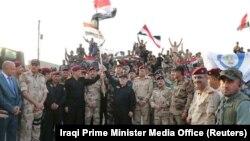 Ирак премьер-министрі Хайдар әл-Абади (ортада оңнан солға бірінші тұрған қарай қара киімдегі) Ирак туын ұстап тұр. Мосул, 10 шілде 2017 жыл.